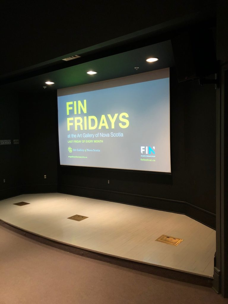 In this image: A FIN Friday's slide projected onto an auditorium screen.