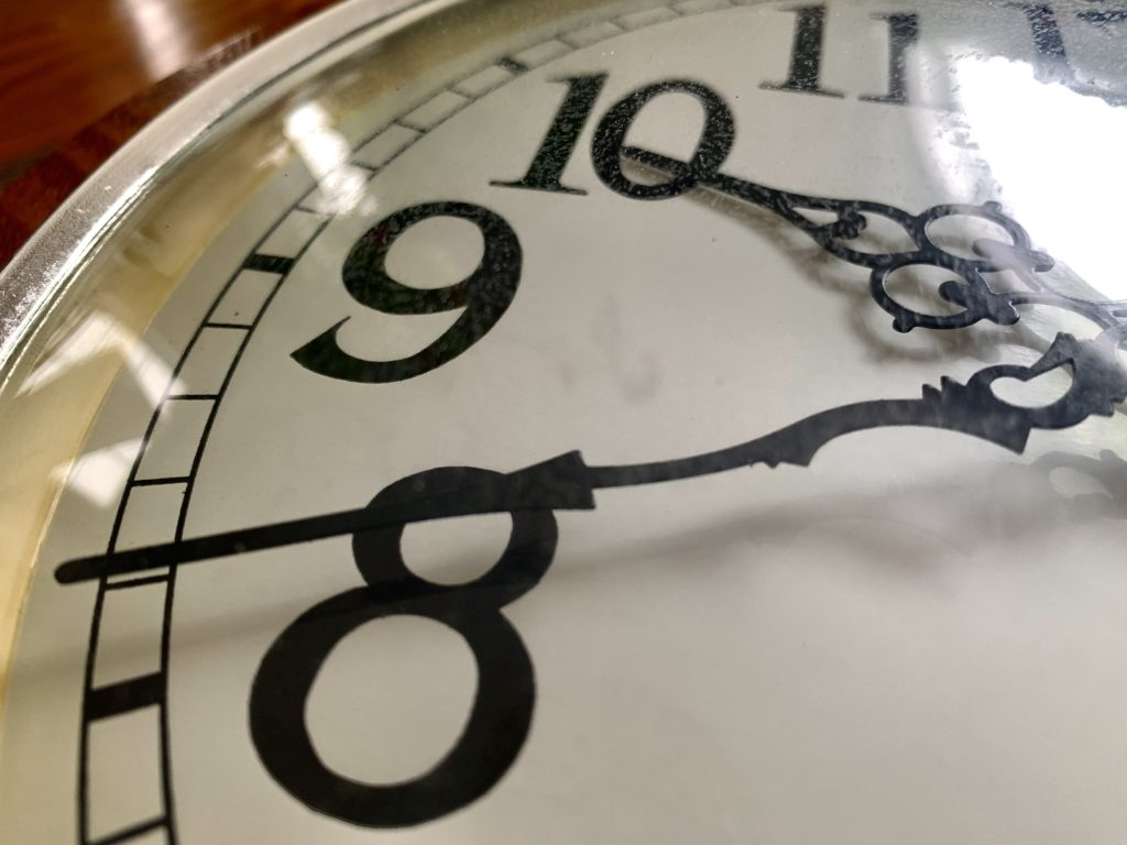In this image: A clock with its hands on 10 and 8.