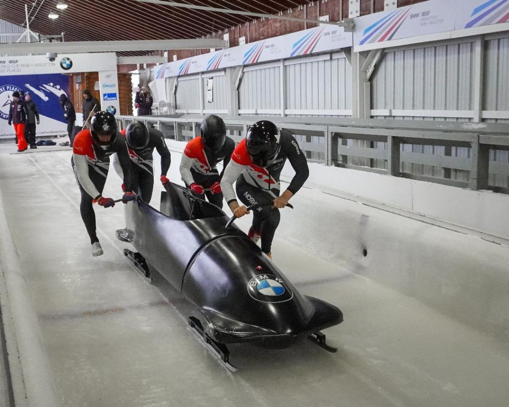 In this image: A bobsled teams pushes off at the start of a track.