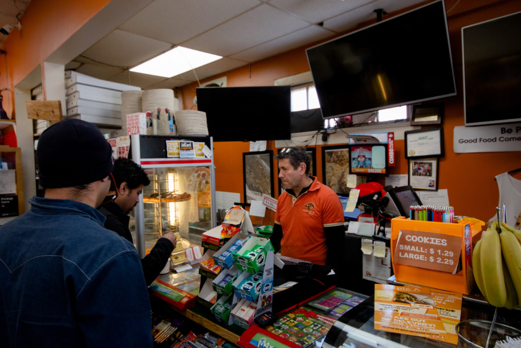 In this image: John Amyoony rings a customer through at the counter.
