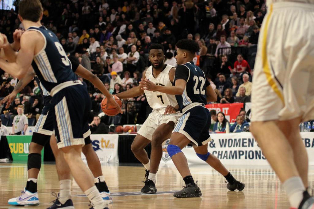 In this image: Jordan Wilson (left) dribbles the basketball.