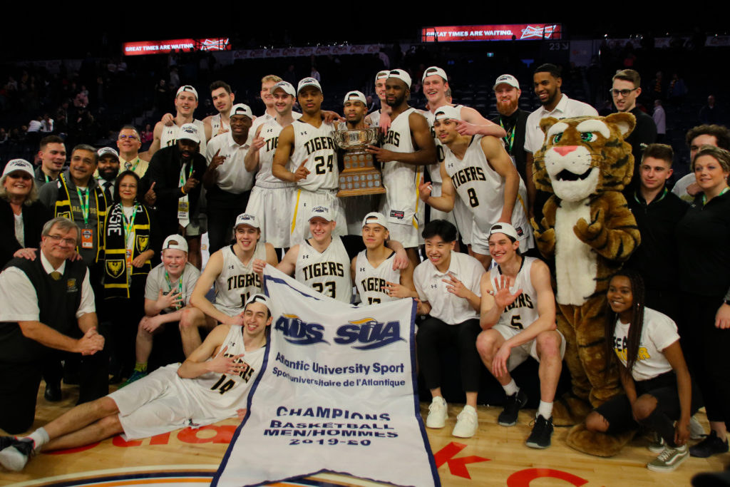 In this image: The Dalhousie men's basketball team and others posing with the AUS champions banner.