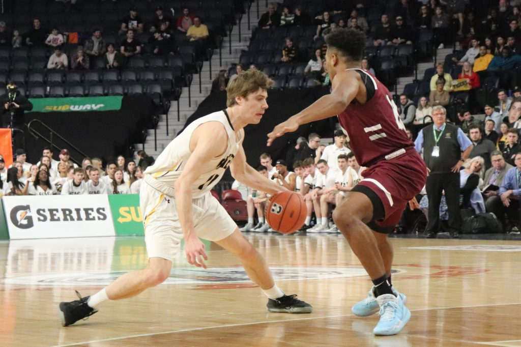 In this image: A Dalhousie Tiger dribbles a basketball against a Saint Mary's Husky.