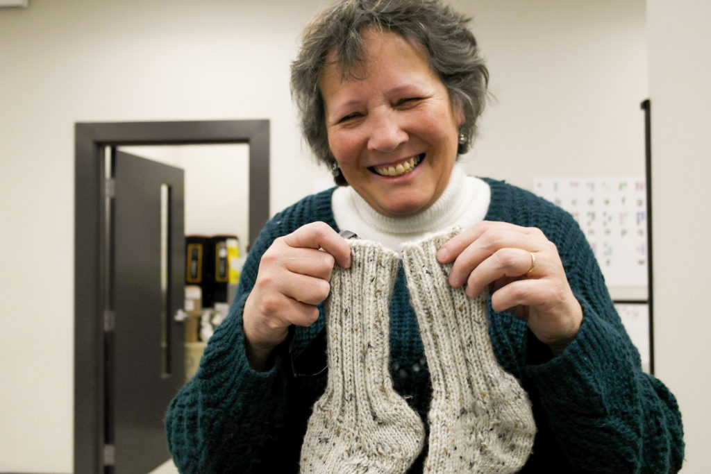 In this image: Irene Swain holds a pair of knitted socks.
