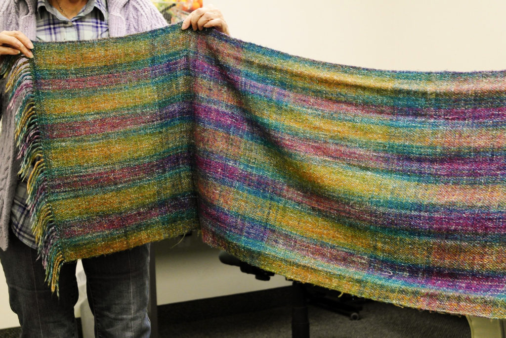In this image: A person holds up a hand-woven scarf made by Helene Comstock.
