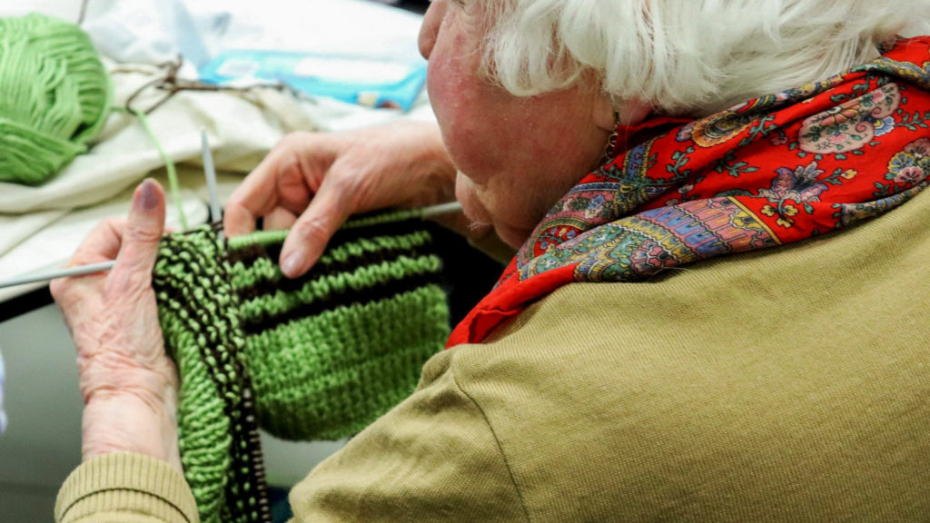 In this image: A participant works on their latest knitting project.