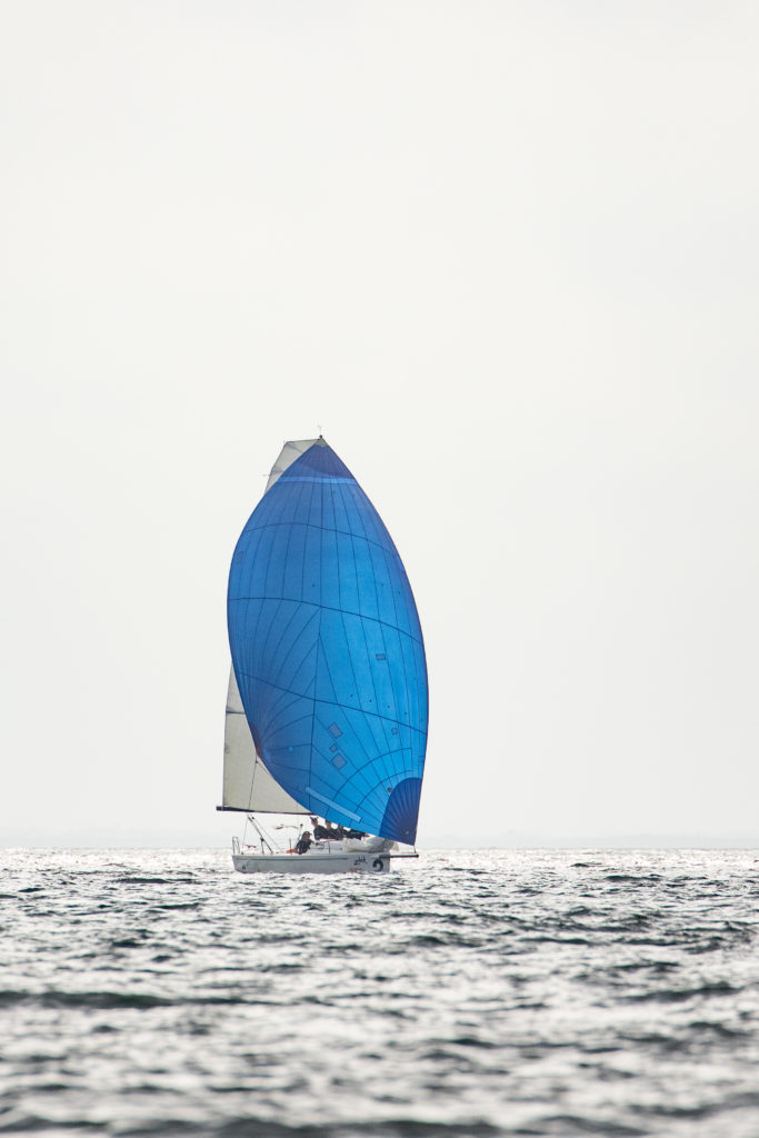 In this image: A sailboat in the distance with a blue sail.