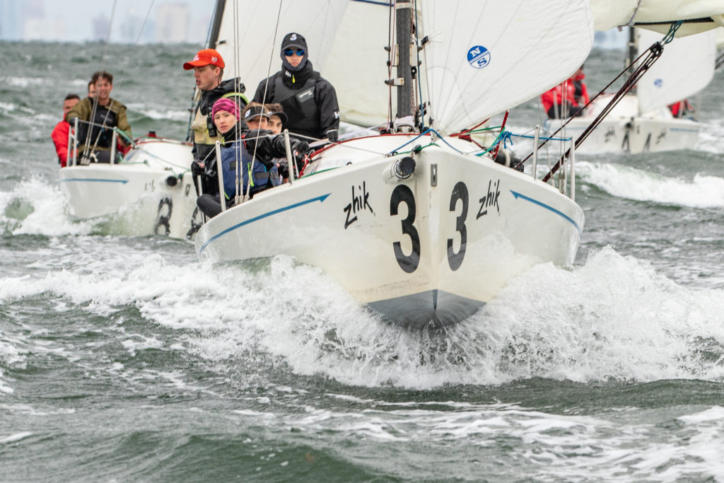 In this image: A group on a sailboat in the water.