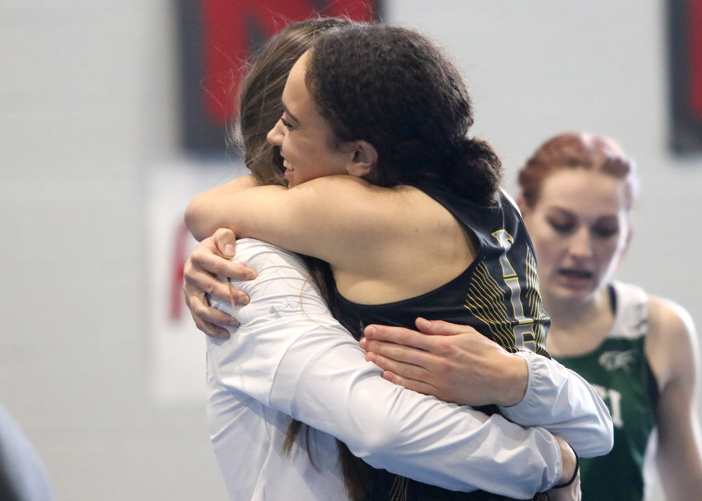 In this image: Maya Reynolds hugs someone after a race.
