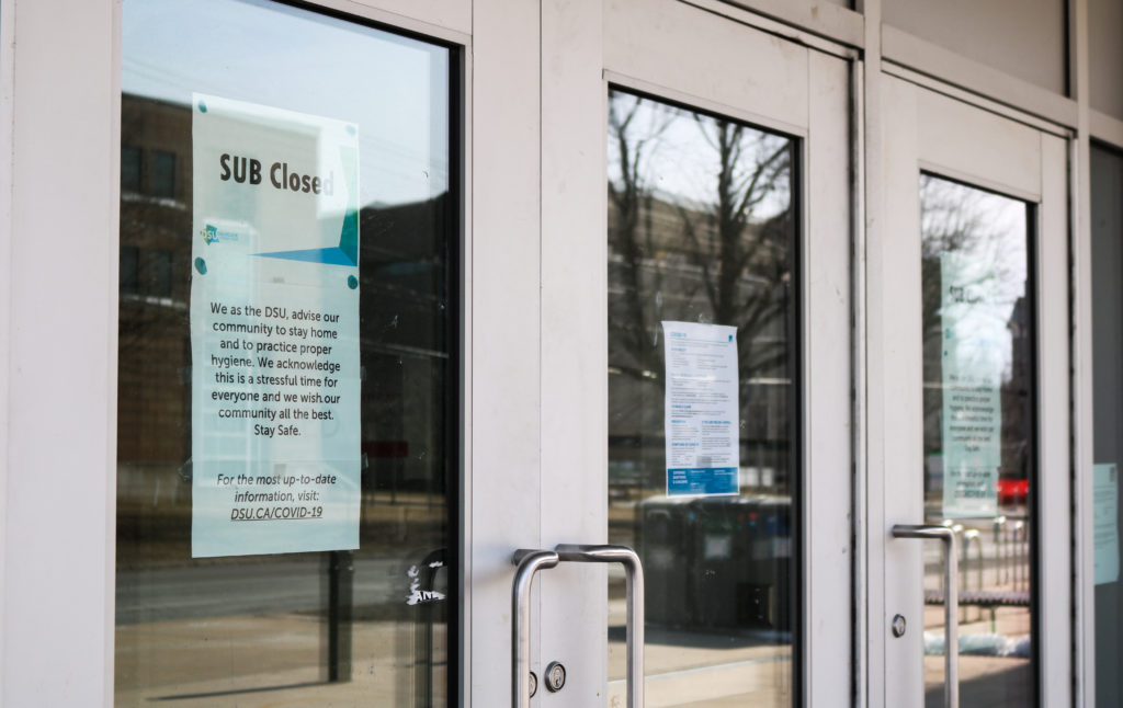 In this image: Signs posted on Dalhousie University's Student Union Building saying it's closed due to COVID-19.