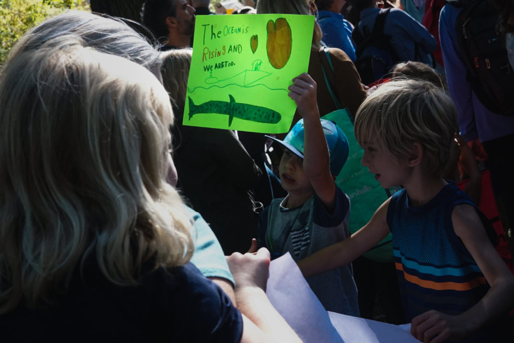 In this image: Two children with one of them holding a green sign.