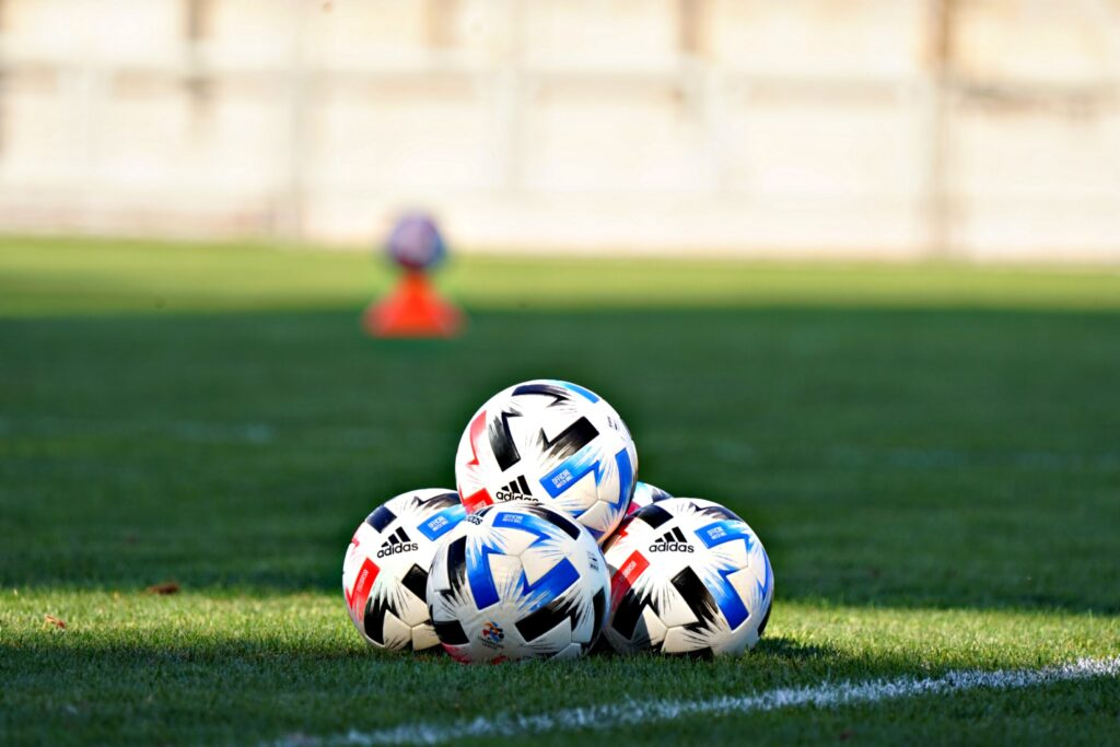 In this image: soccer balls on field