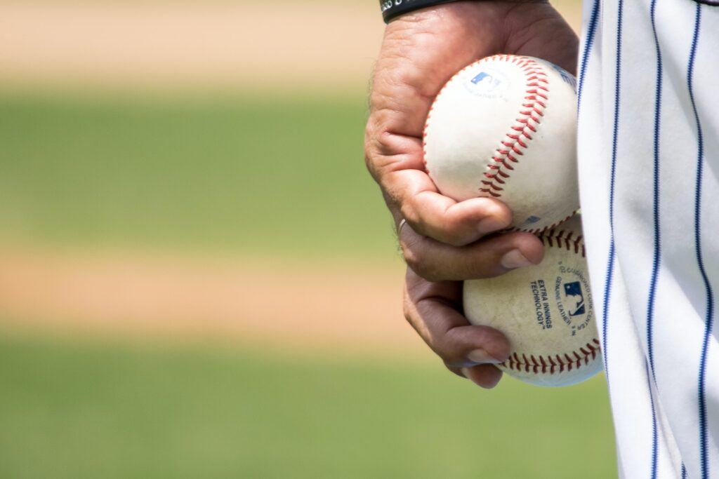 In this image: hand holding baseballs
