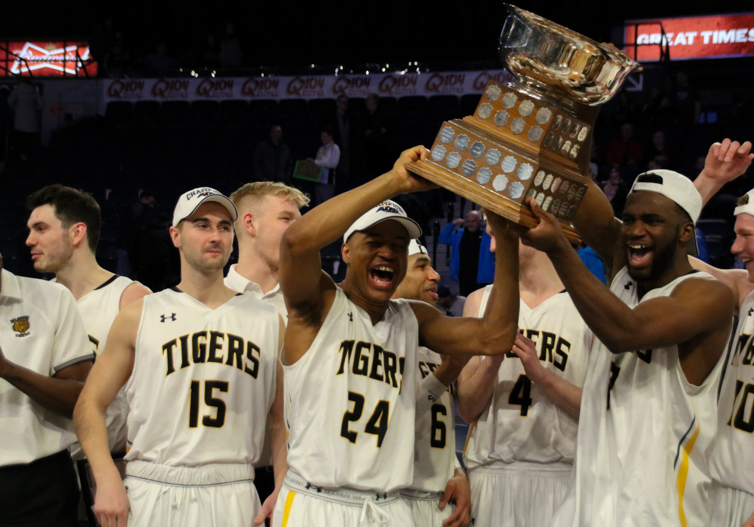 In this image: Shamar Burrows (left) and Jordan Wilson hold the AUS championships trophy among other Tigers.