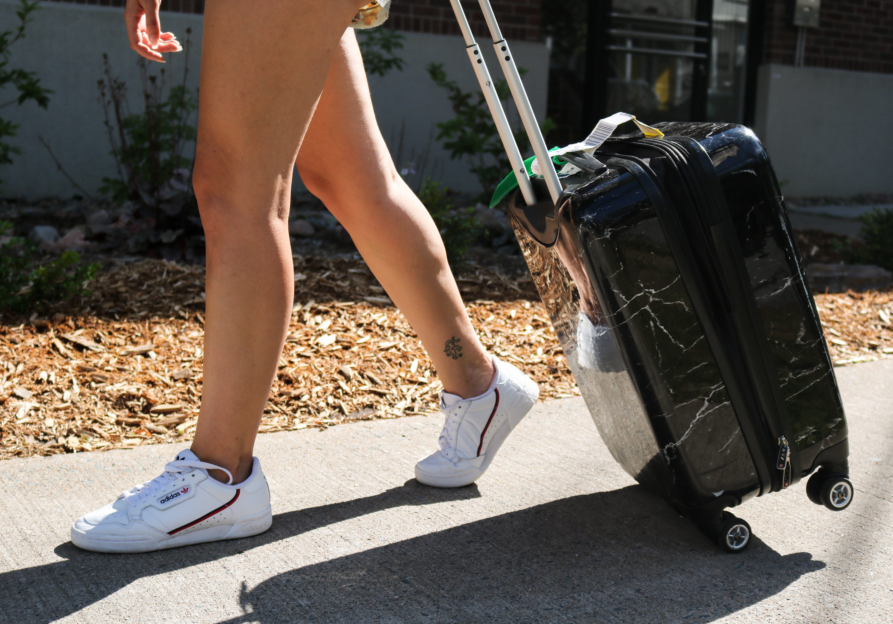 In this image: A girl pulls a dark marble carry-on luggage.