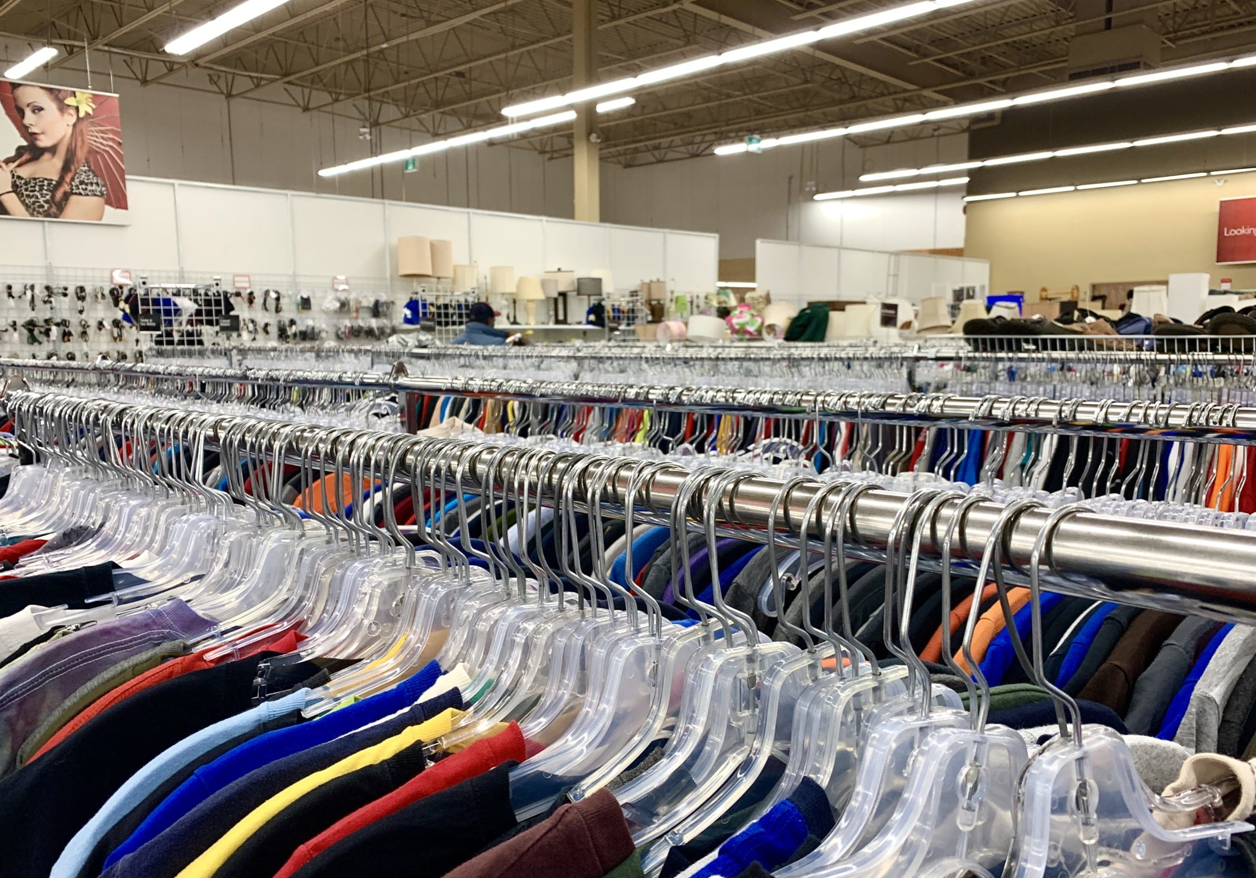 In this image: Racks of clothes at a thrift store.