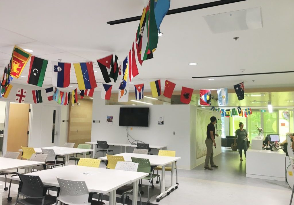 In this image: inside the Dalhousie University International Centre. Different countries' flags hang from the ceiling. A cluster of empty tables and chairs.