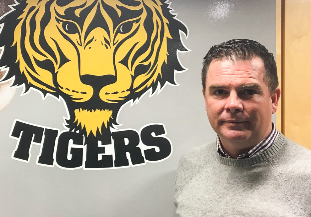 In this image: Tim Maloney beside a Dal Tigers logo.