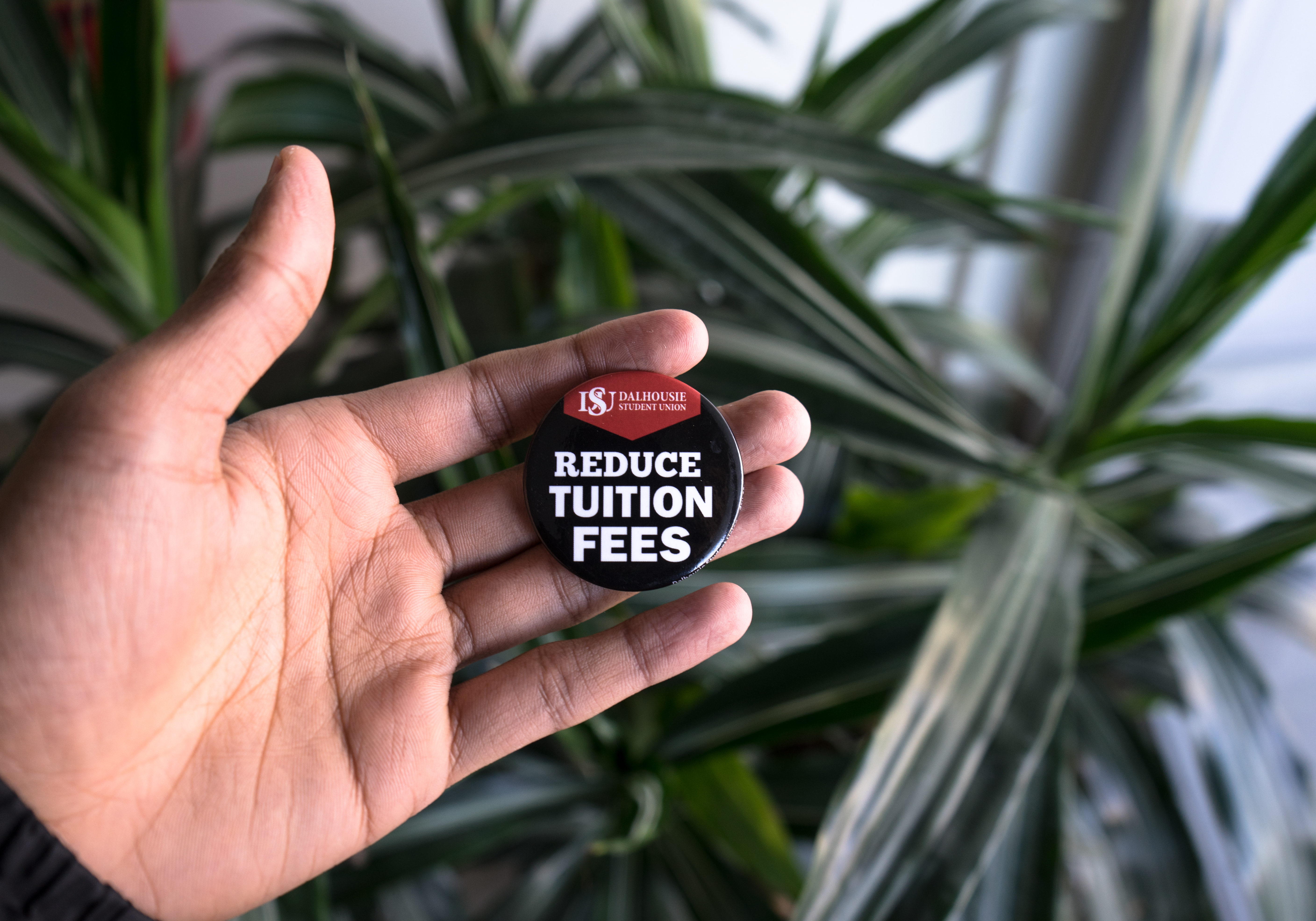 "In this image: Someone holding a ""Reduce tuition fees"" DSU pin."